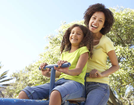 playground ride: Mother And Daughter Riding On Seesaw In Park Stock Photo