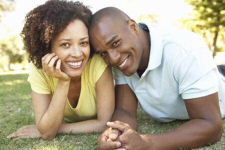 pareja abrazada: Retrato de la joven pareja puesta en c�sped en el Parque  Foto de archivo