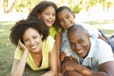 women having fun: Portrait of Happy Family Piled Up In Park Stock Photo