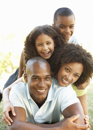 family park: Portrait of Happy Family Piled Up In Park Stock Photo