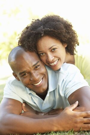 mixed race couple: Portrait Of Young Couple Laying On Grass In Park