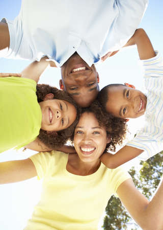 overhead: Portrait of Happy Family Looking Down Into Camera In Park Stock Photo