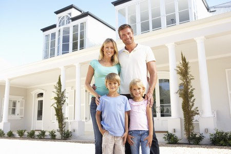 residential homes: Young Family Standing Outside Dream Home Stock Photo
