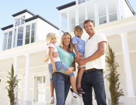 four people: Young Family Standing Outside Dream Home Stock Photo
