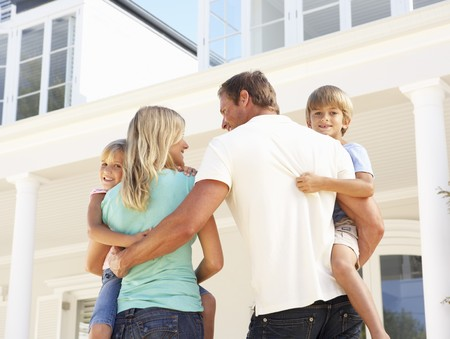 dream home: Young Family Standing Outside Dream Home Stock Photo