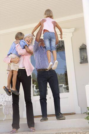 Grandparents Welcoming Grandchildren On Visit To Home Stock Photo - 8198749