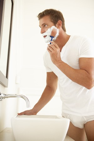 male grooming: Young Man Shaving In Bathroom Mirror