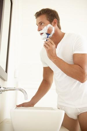 man in underwear: Young Man Shaving In Bathroom Mirror