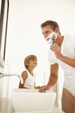 shaving cream: Son Watching Father Shaving In Bathroom Mirror