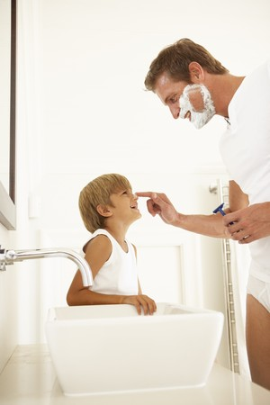 father and son: Son Watching Father Shaving In Bathroom Mirror