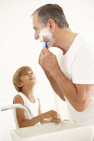 7 year old boys: Grandson Watching Grandfather Shaving In Bathroom Mirror