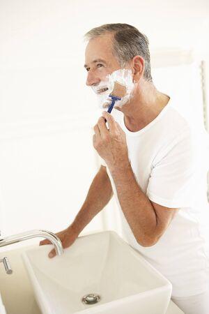 Senior Man Shaving In Bathroom Mirror photo