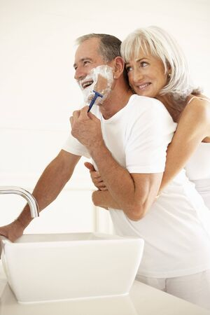 bathroom woman: Senior Man Shaving In Bathroom Mirror With Wife Watching Stock Photo