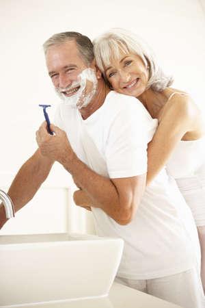hombre afeitandose: Senior afeitada de hombre en el espejo del cuarto de ba�o con esposa Watching  Foto de archivo