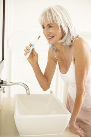 Senior Woman Brushing Teeth In Bathroom Stock Photo - 8198686