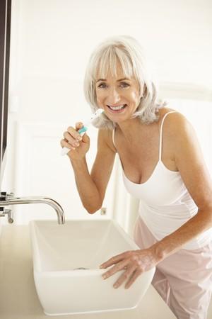 cepillarse los dientes: Mujer Senior cepillarse los dientes en el cuarto de ba�o  Foto de archivo