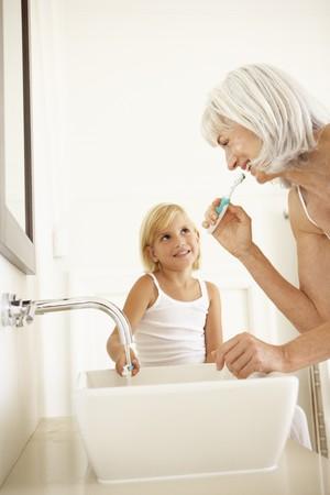 cepillarse los dientes: Abuela cepillarse los dientes en el cuarto de ba�o con la nieta Watching  Foto de archivo