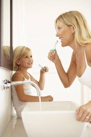 cepillarse los dientes: Madre e hija cepillarse los dientes en el cuarto de ba�o juntos
