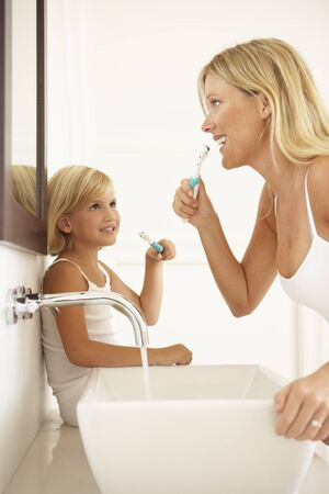 basins: Mother And Daughter Brushing Teeth In Bathroom Together