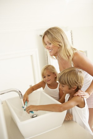7 year old boys: Mother And Children Brushing Teeth In Bathroom Together