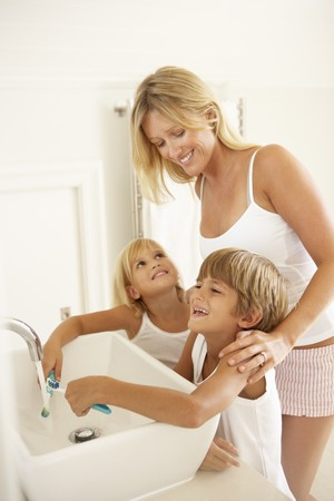 Mother And Children Brushing Teeth In Bathroom Together photo