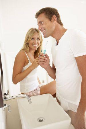 Young Couple Brushing Teeth In Bathroom photo