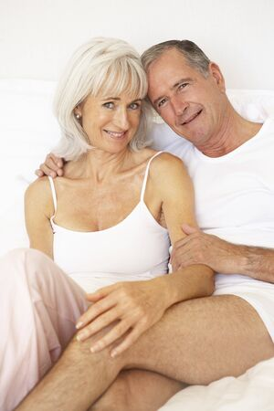 Senior Couple Relaxing On Bed photo