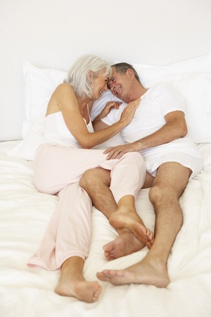mature woman sexy: Senior Couple Relaxing On Bed Stock Photo