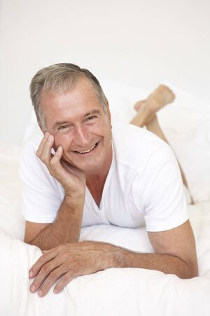 Senior Man Relaxing On Bed Stock Photo - 8198608