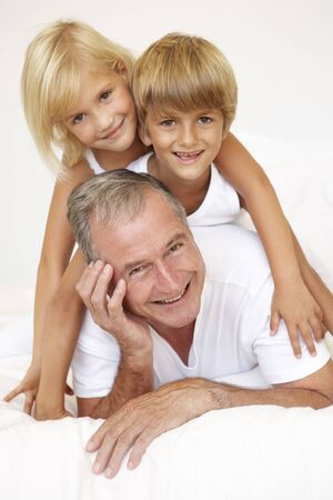 Grandfather Relaxing On Bed With Grandchildren photo