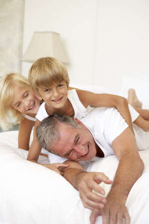 nightclothes: Grandfather Relaxing On Bed With Grandchildren