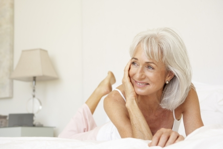 nightclothes: Senior Woman Relaxing On Bed Stock Photo