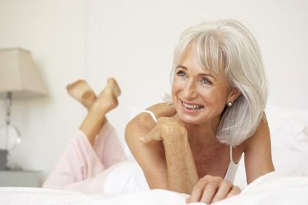 donne mature sexy: Donna anziana rilassante sul letto Archivio Fotografico