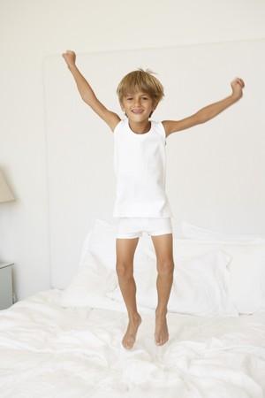 pijama: Joven saltando en la cama