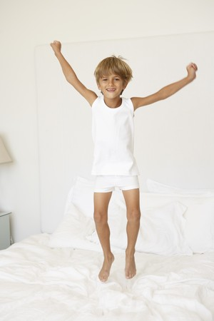 7 year old boys: Young Boy Jumping On Bed Stock Photo