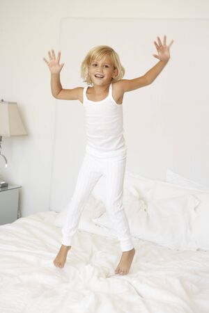 Young Girl Jumping On Bed photo