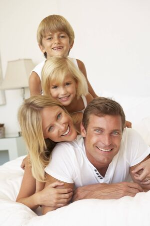 vertical: Portrait Of Young Family Relaxing In Bed Together