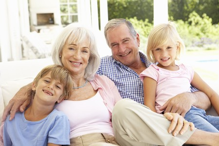 abuelos: Retrato de abuelos con nietos relajante juntos en el sof�  Foto de archivo