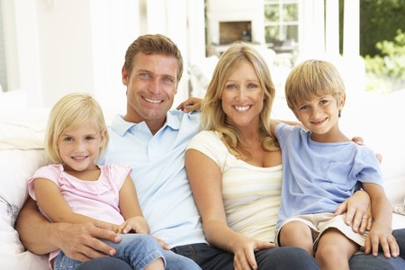 family living: Portrait Of Young Family Relaxing Together On Sofa Stock Photo