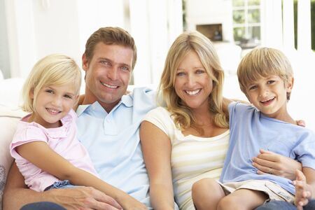 husbands: Portrait Of Young Family Relaxing Together On Sofa Stock Photo