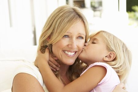 love kissing: Daughter Giving Mother Kiss Relaxing On Sofa Stock Photo