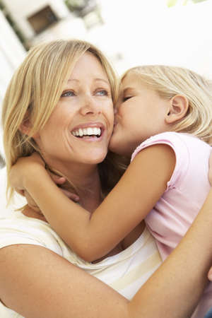 Daughter Giving Mother Kiss Relaxing On Sofa photo