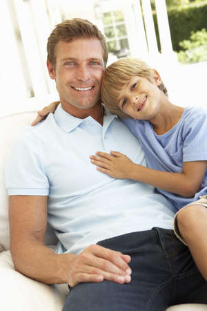 Portrait Of Father And Son Relaxing On Sofa Stock Photo - 8198785