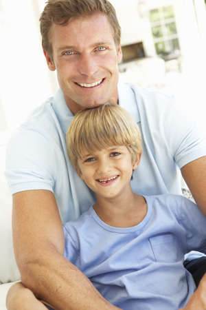 Portrait Of Father And Son Relaxing On Sofa Stock Photo - 8198837
