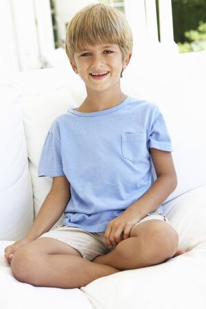 boy sitting: Portrait Of Young Boy Relaxing On Sofa Stock Photo