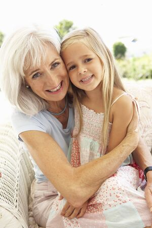 Portrait Of Grandmother With Granddaughter Relaxing Together On Sofa photo