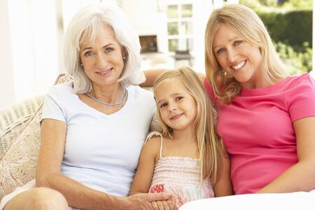 three generation: Portrait Of Grandmother, Daughter And Granddaughter Relaxing On Sofa