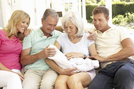 Extended Family Relaxing Together On Sofa With Newborn Baby photo