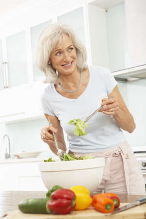 Senior Woman Preparing Salad In Modern Kitchen photo