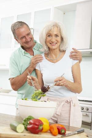 Senior Couple Preparing Salad In Modern Kitchen Stock Photo - 8198682